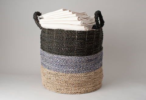 Classic natural cotton sheets stacked in weave basket.