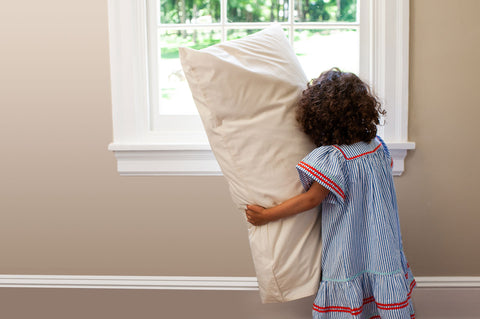 Toddler holding classic cotton pillowcase.