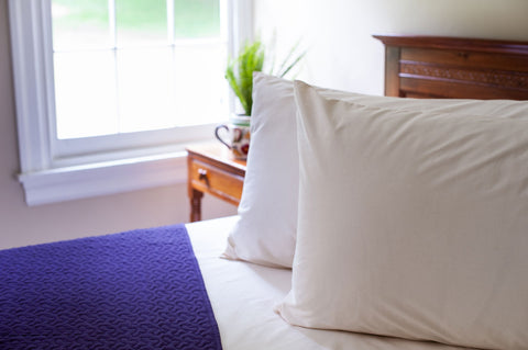 Organic, all-natural pillowcases styled on bed with violet bedspread.
