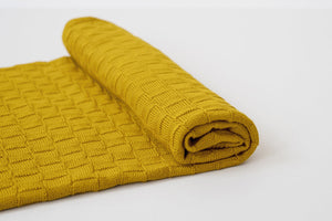 American Made Organic Cotton Baby Blanket in Turmeric Partially rolled up