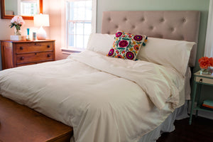 Organic cotton duvet cover set and pillow shams in natural color on a freshly made bed in a bedroom.