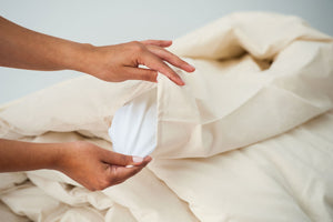 Organic cotton duvet cover with women's hand showing duvet insert in natural color.
