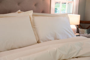 Organic cotton pillow shams with pillows on a made bed in natural color.