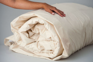 Organic cotton duvet cover in natural color rolled up with insert.