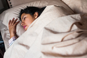 Woman asleep in bed with her head on Organic Pillowcase with Pillow covered by Organic Sheets.