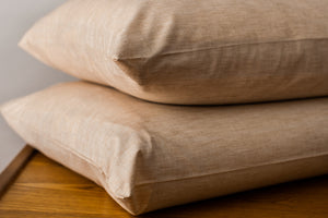 2 Organic Pillowcases with Pillows stacked on a side table.