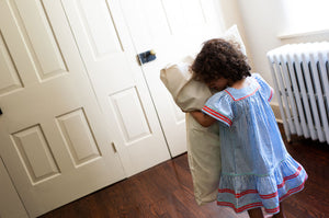 Little girl snuggling organic cotton pillowcases to her face standing up in a bedroom.