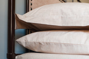 2 Organic Pillowcases with Pillows stacked on a side table