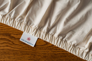 Organic cotton fitted sheet in natural color showing american blossom linens tag.