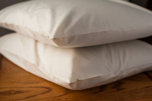 2 pillows in organic cotton pillowcases stacked on a night stand.