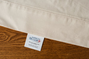Flat organic cotton sheet in natural color displaying american blossom linens tag.