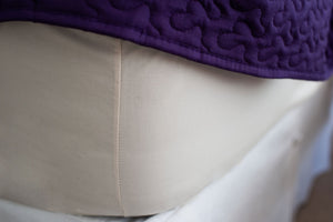 Corner of mattress made with organic cotton fitted sheet in natural color with a purple bedspread.