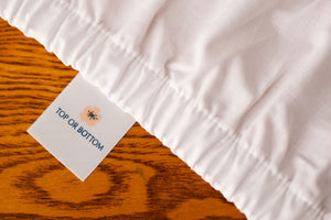 Organic cotton crib sheets in white color showing american blossom linens tag.