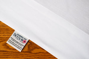 Flat organic cotton sheet showing american blossom linens tag.