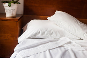 Unmade bed with organic cotton sheets in white color.