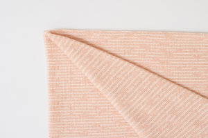 American Made Organic Beach Throw in Peach folded at the corner.