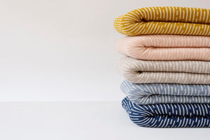 American Made Organic Beach Throws in Turmeric, Peach, Dove Grey, Light Indigo and Dark Indigo folded and stacked.