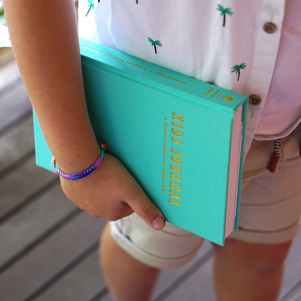 truly amor kids journal boy holding the aqua book