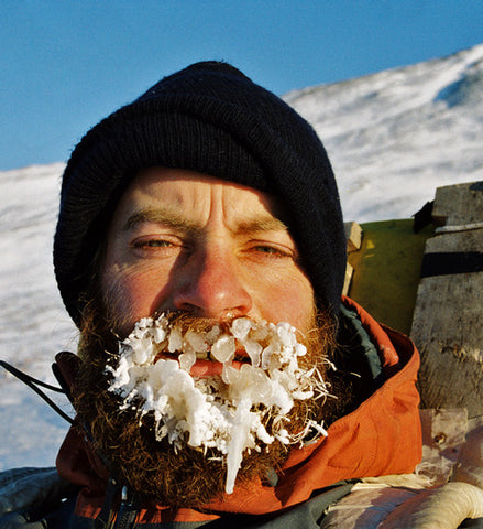 A headshot of a man wearing a black toque and orange jacket. His beard is covered in ice from his breath condensation freezing. The hill in the background is covered in snow.