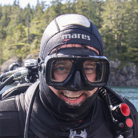 Headshot of a man smiling. He is wearing full cold water dive gear, including goggles, head covering, and drysuit. In the background is ocean and forest.