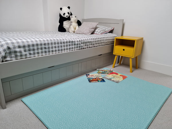 Medium play mat alongside single bed in child's bedroom