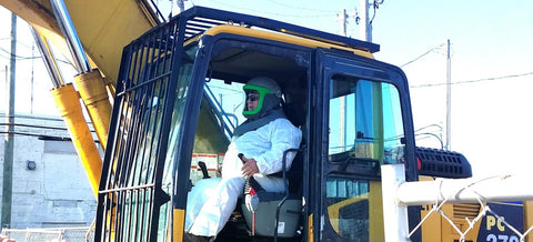 Demolition crane operator wears respiratory protection to reduce asbestos exposure on the job in Detroit