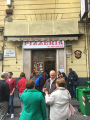 front door view of pizzeria da michele in naples italy with people waiting to get in