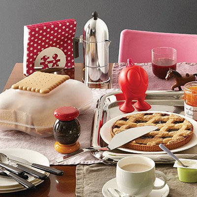 Alessi La Cupola stovetop espresso maker surrounded by a pie, cup of coffee, cookbooks etc.