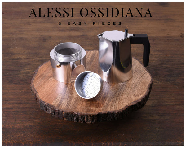 Alessi Ossidiana espresso maker taken apart into its three pieces sitting on a tray