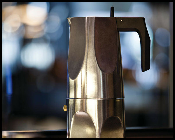 Alessi Ossidiana espresso maker with blurred lights in the background