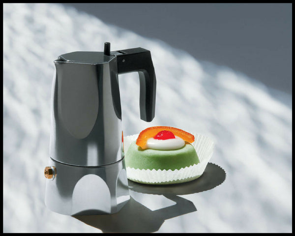 Alessi Ossidiana espresso maker beside a green dessert with a candied orange peel on top