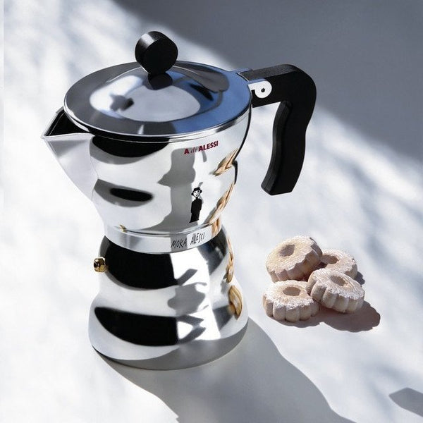 Alessi Moka - Stove-top Espresso Coffee Maker on a white counter with small circular cookies beside it
