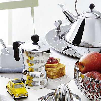 Alessi Moka - Stove-top Espresso Coffee Maker surrounded by a yellow car, toast, fruit and tea kettle