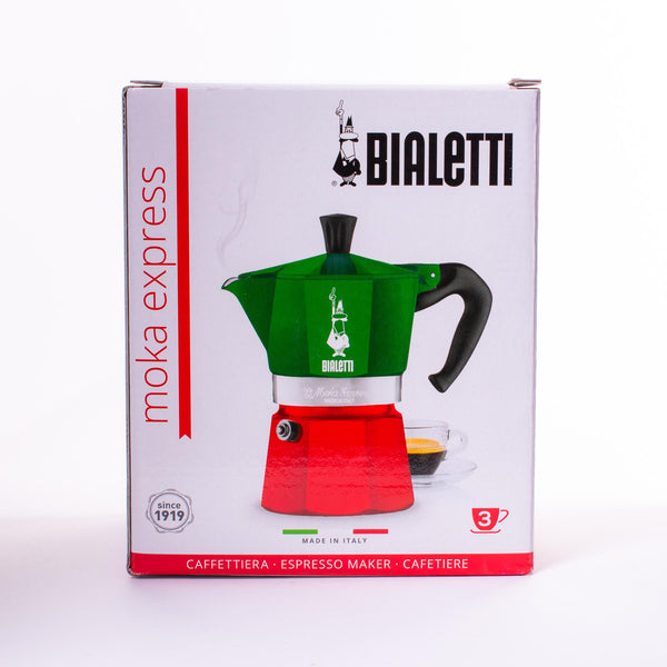 Front view the box of the Bialetti Moka Tricolor with red bottom, green top and silver middle band with a red sash on it and the white logo on the green.