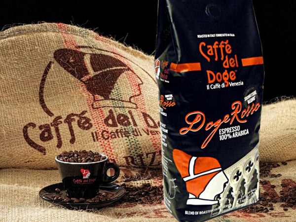 A package of Caffe Del Doge Rosso standing up in front of a burlap bag with their logo and an espresso cup full of coffee beans