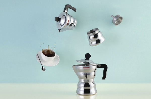 Alessi Moka - Stove-top Espresso Coffee Maker against a blue background with a cup of coffee and its various pieces in the air above it