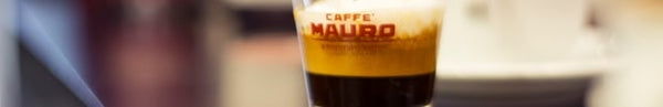 caffe mauro italian coffee in a glass cup with the words on the front