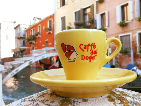 yellow cup with caffe del doge logo on it, sitting on the stone railing of a bridge over a canal in venice italy