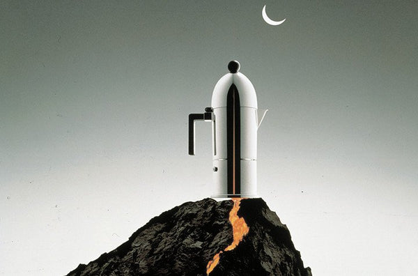 Alessi La Cupola stovetop espresso maker on top of a rock with a moon in the distance