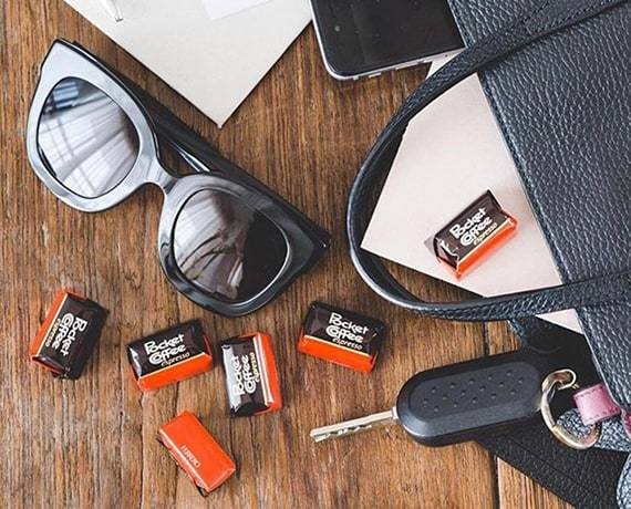 pocket coffee, individual pieces on a table with sunglasses and keys and a purse