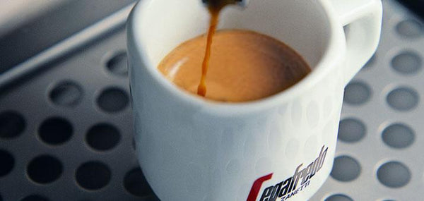 white cup with segafredo written on it on an espresso machine with coffee dripping into the cup