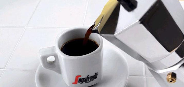 white cup and saucer with segafredo written on it getting coffee poured into it from a silver moka pot