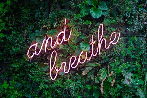 and breathe neon sign | Whisper
