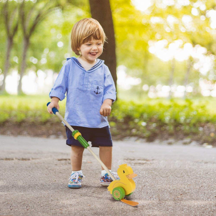 boy in blue playing with Push-n-Pull Waddling Duckling