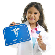 little girl in a white coat with Dr. Maple's Medical Kit