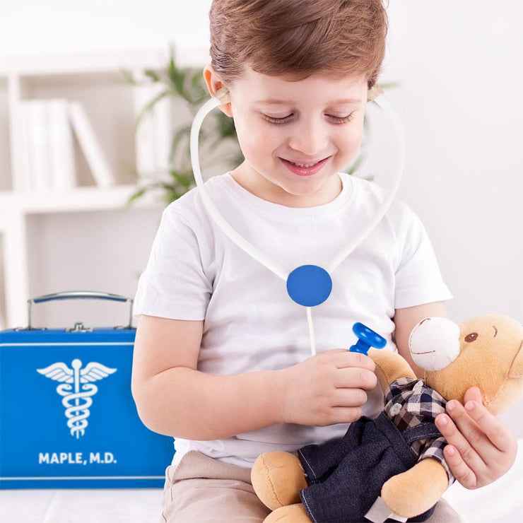 little boy using the stethoscope on his teddy