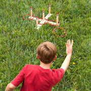 boy playing ring toss on green grass throwing ring