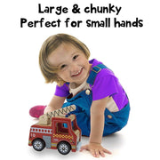 pretty little girl pushing wooden fire engine on white backing