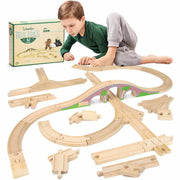 young boy laying on his side playing with a built train track box packaging seen behind him