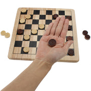 hand holding a brown wooden checker above a checkers board